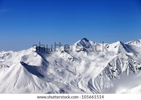 Snowy mountains and blue sky. Caucasus Mountains, Georgia, region Gudauri. - stock photo