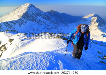Snowy mountains and hiker ascending with trekking pole - stock photo