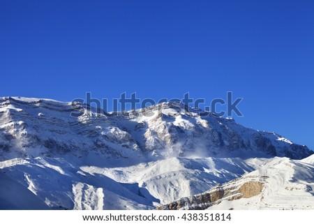Snowy mountains at sun windy day. Greater Caucasus, Mount Shahdagh, Qusar rayon of Azerbaijan. - stock photo