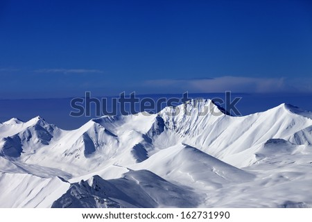 Snowy mountains at sunny day and multicolor blue sky. Caucasus Mountains, Georgia, ski resort Gudauri.