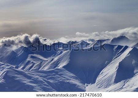 Snowy mountains at winter evening. Caucasus Mountains, Georgia, view from ski resort Gudauri. - stock photo