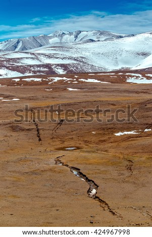 Snowy mountains. crack after an earthquake. Severe mountains peaks covered by snow. Russia, Siberia, Altai mountains, Chuya ridge. - stock photo