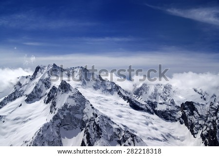 Snowy mountains in clouds. Caucasus Mountains, view from ski resort Dombay. - stock photo