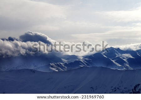 Snowy mountains in haze at sunny evening. Caucasus Mountains, Georgia, view from ski resort Gudauri. - stock photo
