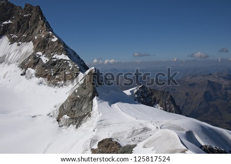 Snowy mountains with valley below in background - stock photo