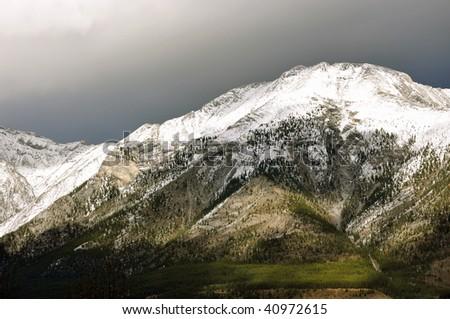 Snowy moutain, green grass, dark sky - stock photo
