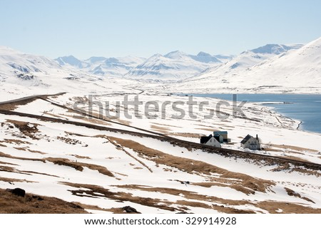 Snowy northern landscape with mountains and little farm houses. Iceland. - stock photo
