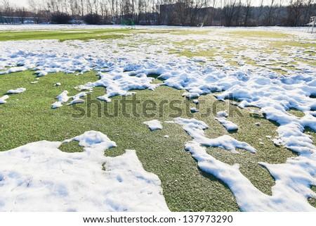 snowy outdoor soccer field in spring low season - stock photo