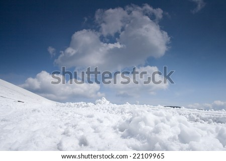 Snowy path with blue sky and clouds