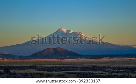 Snowy peak of Mt. Shasta, CA, during sunset.