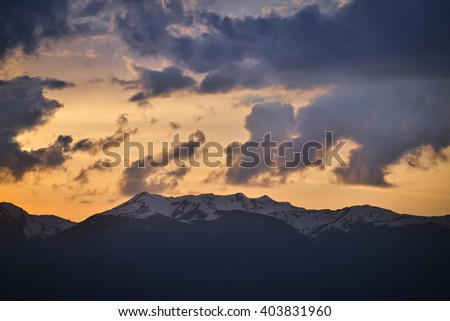 Snowy peak of the mountain and cloudy sky during the sunset - stock photo