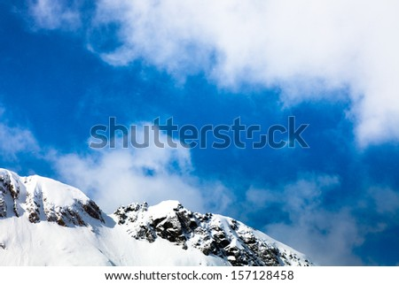 Snowy peaks against the blue sky and falling snow - stock photo