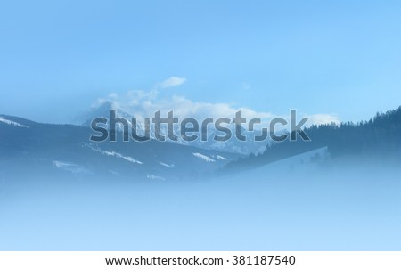 Snowy peaks at foggy morning. The glacier 'Dachstein' is located at the north Alps in Austria. Photo taken from 'Radstadt'. - stock photo