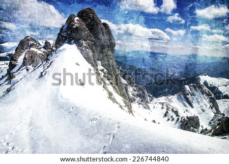Snowy peaks of a mountain in winter on a grungy background - stock photo