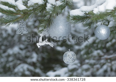 Snowy pine tree branches with sparkling reindeer ornament and Christmas baubles at snowy wood background - stock photo