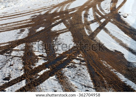 Snowy road and dirty tire tracks. Background and texture. - stock photo