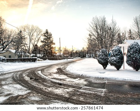 snowy road in a residential neighborhood - stock photo