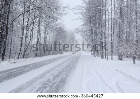 Snowy road in winter woods with a car
