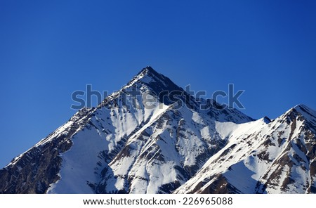 Snowy rocks in evening. Caucasus Mountains, Georgia, view from ski resort Gudauri. - stock photo