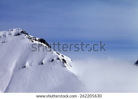 Snowy rocks in fog. Caucasus Mountains, Georgia, ski resort Gudauri. - stock photo