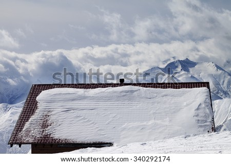 Snowy roof and mountains in clouds. Caucasus Mountains, Georgia, ski resort Gudauri. - stock photo