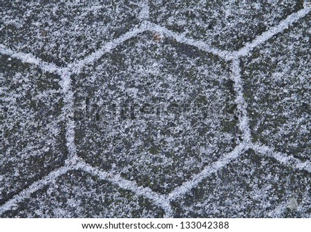 Snowy sidewalk with hexagon stones close-up