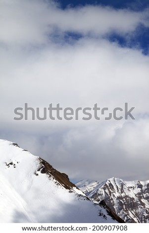 Snowy slope and sky with clouds at sun day. Caucasus Mountains, Georgia, view from ski resort Gudauri.