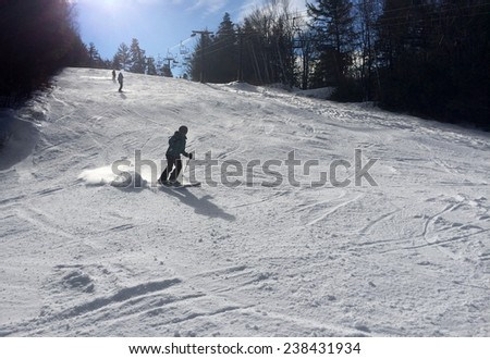 Snowy slope in the mountains with random skiers - stock photo