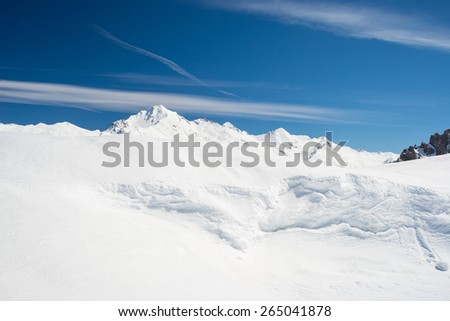 Snowy slope shaped by the wind with snowdrift on the ridge and majestic view of snowcapped high mountain peaks in the italian alpine arc, in a bright sunny day of spring, Torino Province, Italy. - stock photo