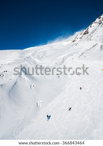 Snowy slopes in winter mountains with skiers. Skiing resorts - stock photo