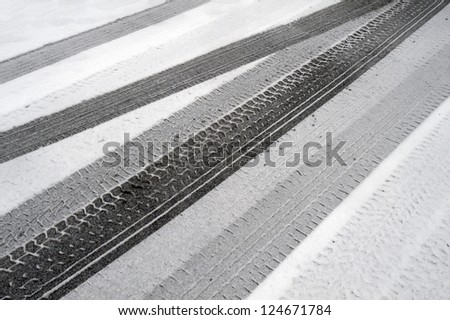 Snowy tire tracks on the winter road - stock photo