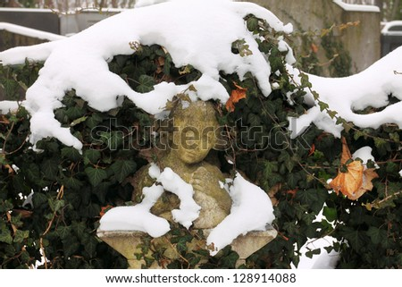 Snowy Tombstone with Girl at the Prague Jewish Cemetery, Czech Republic - stock photo