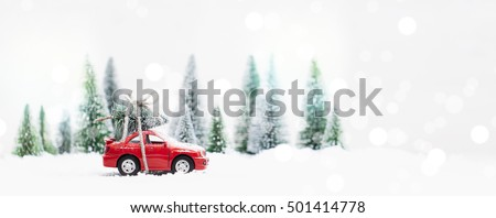 Snowy Winter Forest with miniature red car carrying a  christmas tree and presents