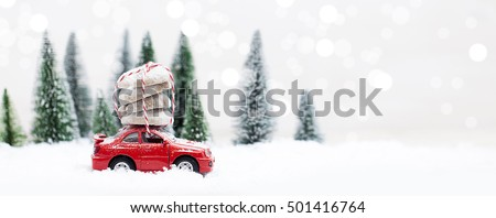 Snowy Winter Forest with miniature red car carrying Christmas Cookies