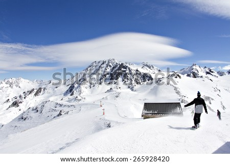 Snowy winter landscape of a ski resort in the Alps with a snowboarder about ride down the piste. - stock photo