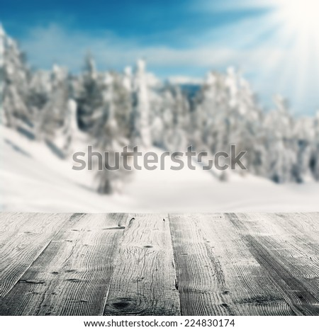 Snowy winter landscape with empty wooden planks - stock photo
