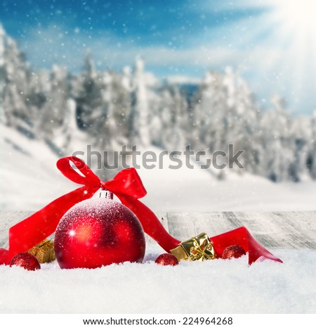 Snowy winter landscape with red christmas balls - stock photo
