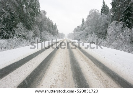 Snowy winter road among frozen forest after sleet. Cold weather, snowfall, slippery road, bad visibility.