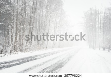 Snowy winter road during blizzard in Latvia. Heavy snow storm. - stock photo