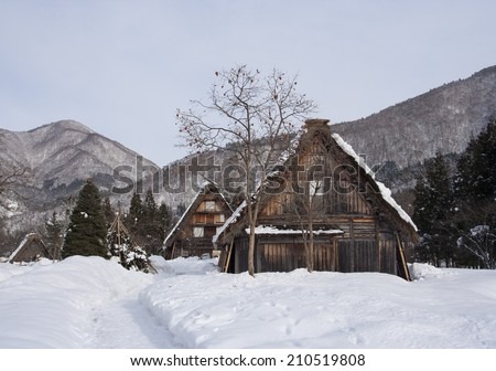 Snowy winter scene with Japanese thatched roof houses and persimmon tree - stock photo