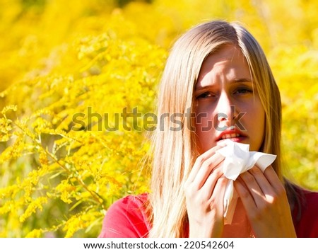 Snuffling young woman because of pollen allergy. - stock photo