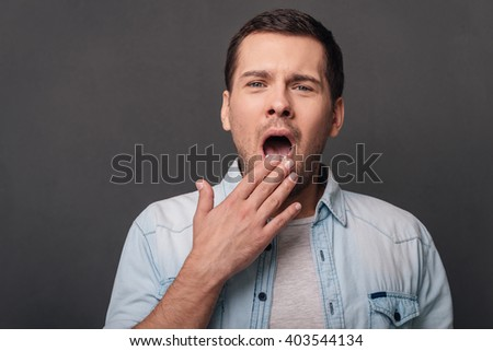So bored! Young handsome man covering mouth by hand and yawning while standing against grey background - stock photo