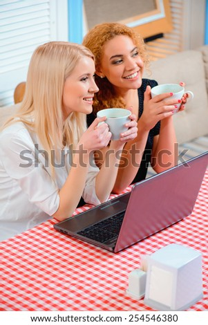 So glad we get to study together. Top view of two young women working on laptop and drinking coffee smiling while sitting on the couch of the cafe - stock photo