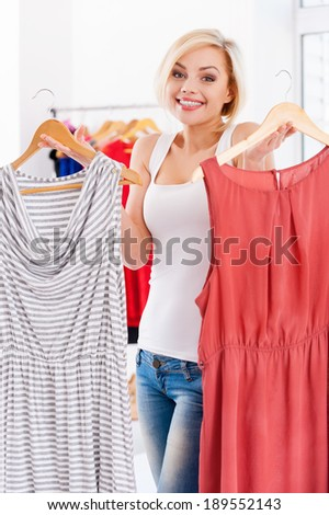 So hard to choose! Attractive young blond hair woman holding two dresses and looking at camera