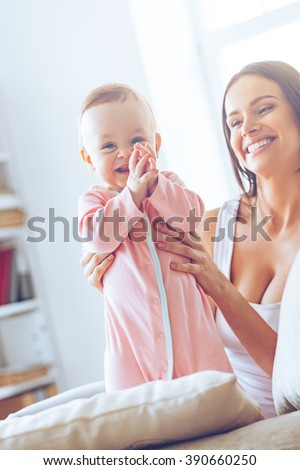 So interesting to explore my home with mommy! Cheerful little baby girl looking at camera and clapping while her mother holding her and sitting on the couch at background - stock photo