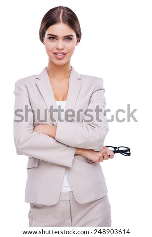 So much beauty in business. Confident young businesswoman keeping arms crossed and smiling while standing against white background - stock photo