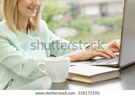 So much to do! Selective focus on a smiling female typing on her laptop over the cup of coffee
