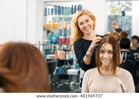 So what are we going for? Cheerful hairdresser working with her client at the beauty salon