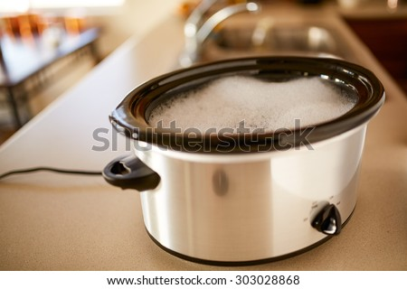 soaking slow cooker in soapy water on low heat kitchen hack - stock photo