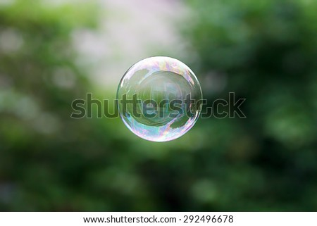 Soap ball in daylight against a background of greenery.